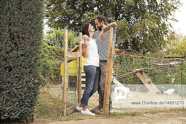 Glückliches Paar steht am Hühnerstall im Garten