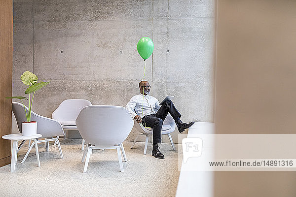 Mature businessman with green balloon sitting on armchair using digital tablet