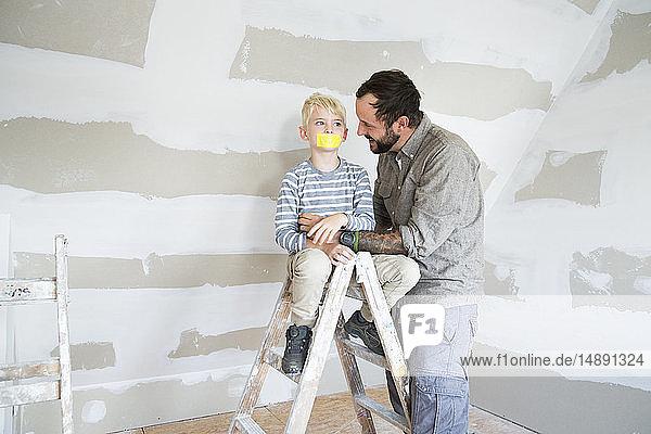 Vater sieht Sohn auf Leiter mit zugeklebtem Mund an