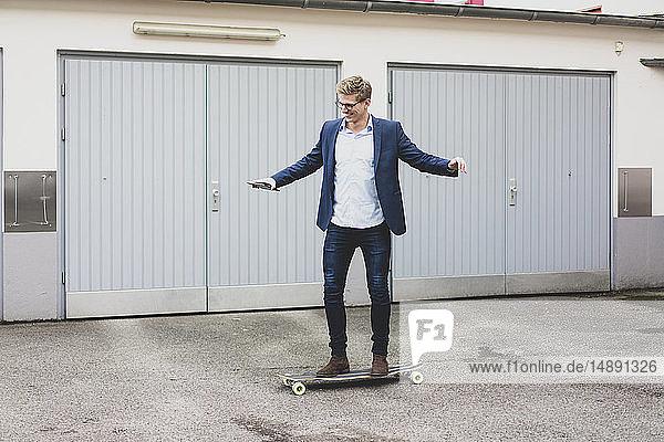 Young businessman riding skateboard at garage door