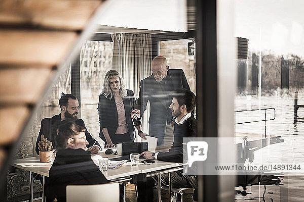 Kreative Geschäftsleute  die eine Teambesprechung in ihrem Hausboot-Büro abhalten
