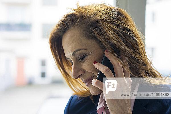 Rothaarige Geschäftsfrau spricht am Telefon