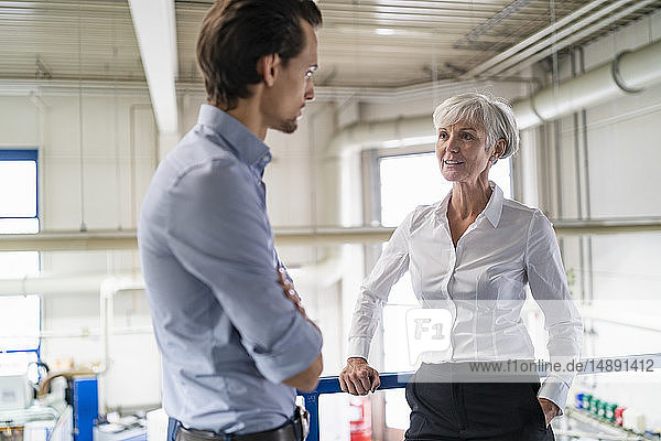 Businessman and senior businesswoman talking in a factory