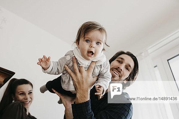 Glückliche Familie spielt mit Mädchen zu Hause
