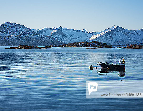Fishing boat by snow covered mountains in Tromso  Norway
