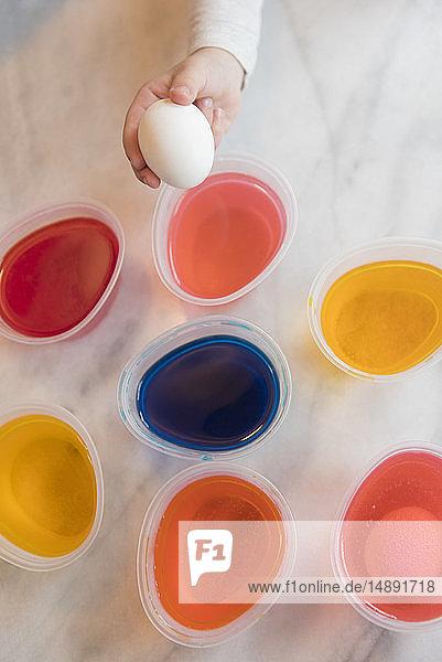 Hand of girl selecting dye for Easter egg