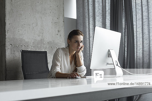 Frustrated businesswoman working at desktop computer