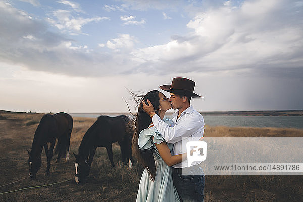 Young couple kissing in field by horses