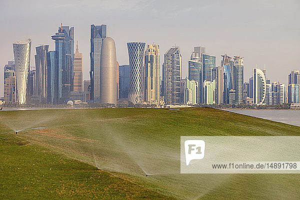 Sprinkler system on lawn by skyline of Doha  Qatar