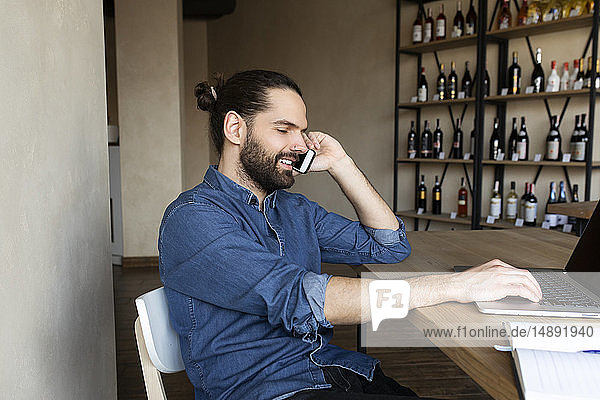 Young businessman on phone by laptop