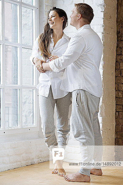 Smiling couple embracing by window