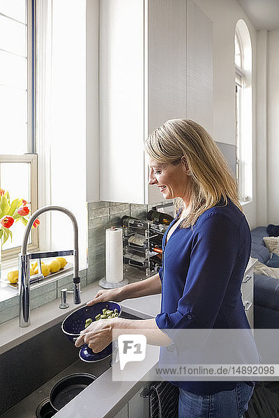 Woman washing vegetables in colander
