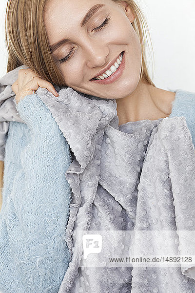 Smiling woman feeling soft fabric on her cheek