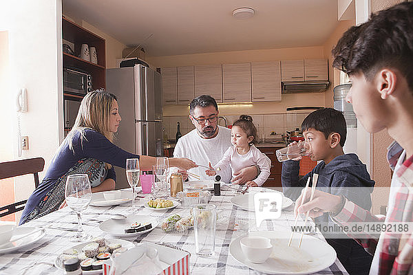 Family eating sushi at dining table