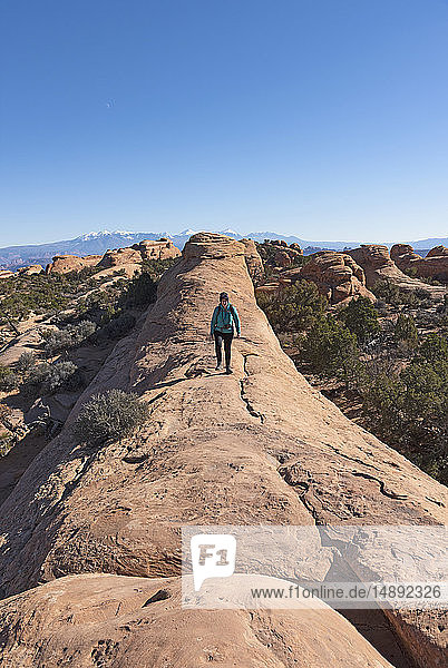 Woman hiking on rock in Arches National Park  Utah  USA