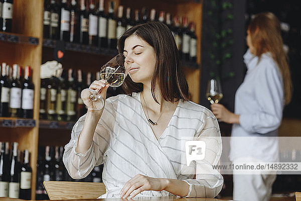 Young woman smelling white wine