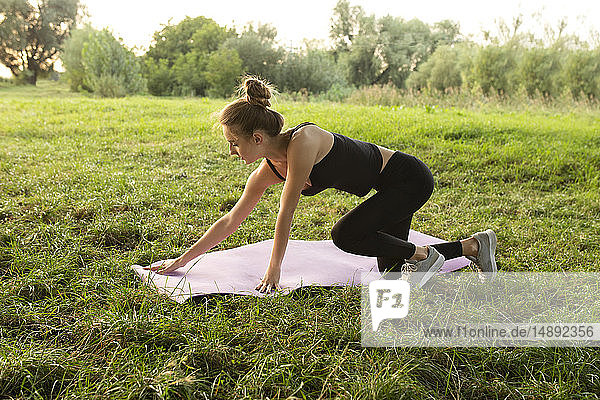 Young woman placing yoga mat in park
