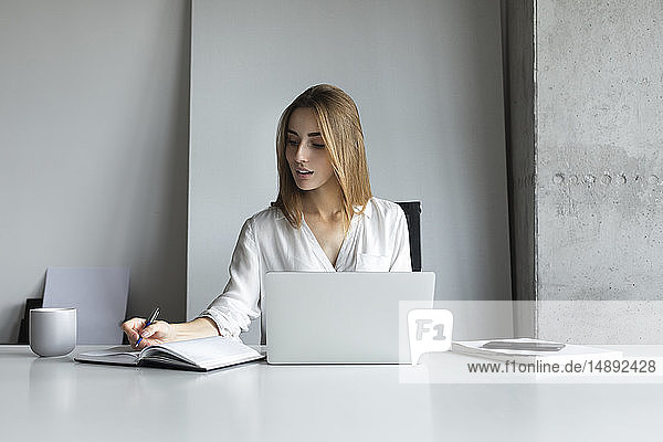 Young businesswoman writing notes while working on laptop