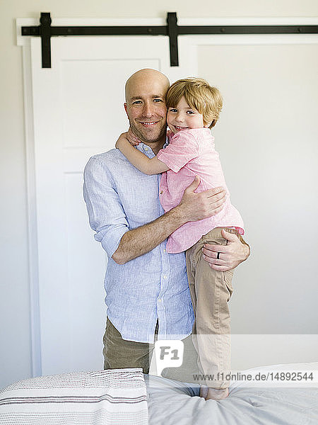 Father and son hugging in bedroom