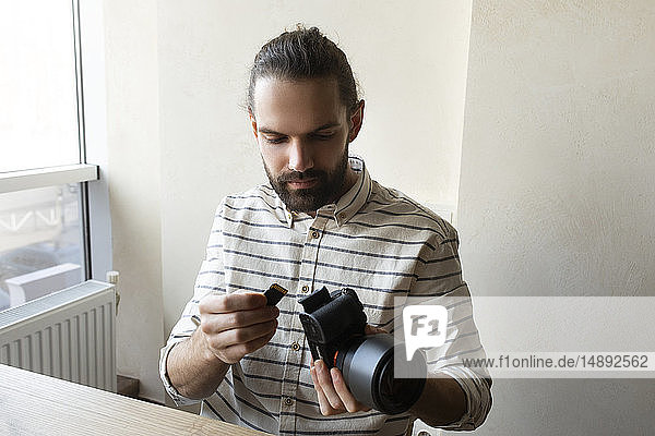 Young man holding camera and SD card
