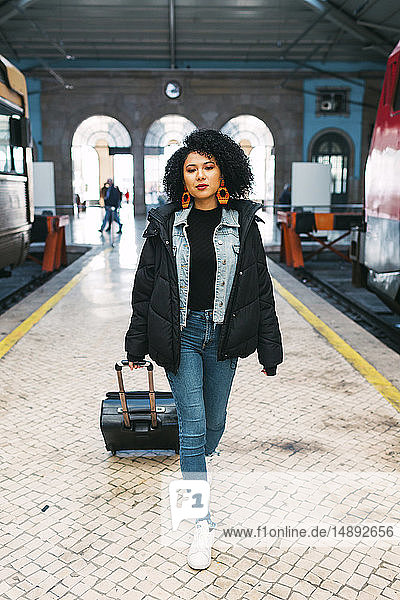 Young woman pulling suitcase in railway station