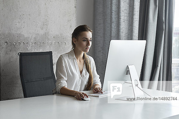 Young businesswoman working on desktop computer