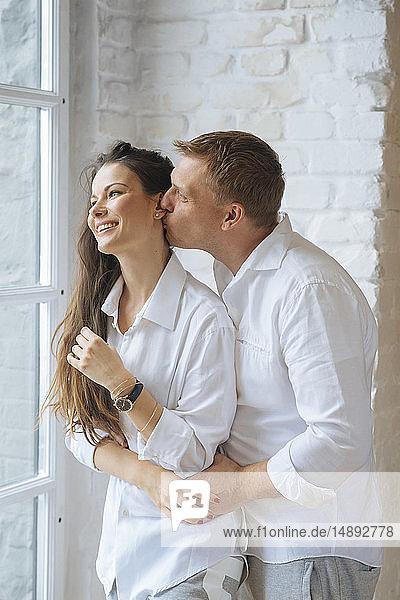 Man kissing wife's cheek