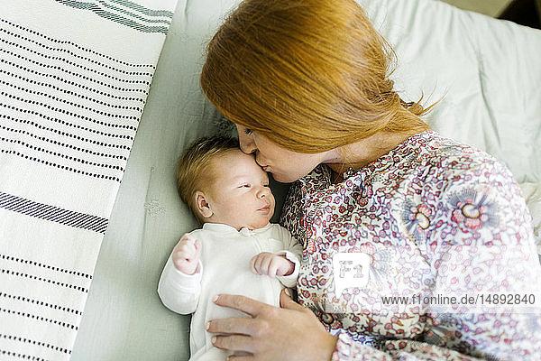 Woman kissing her newborn son's head