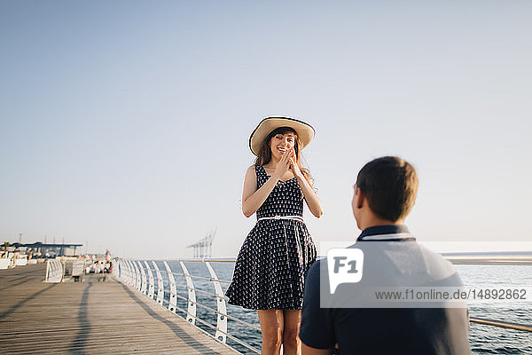 Man proposing to woman on pier