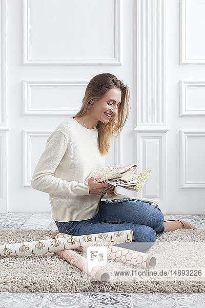 Woman sitting on rug with variety of fabrics