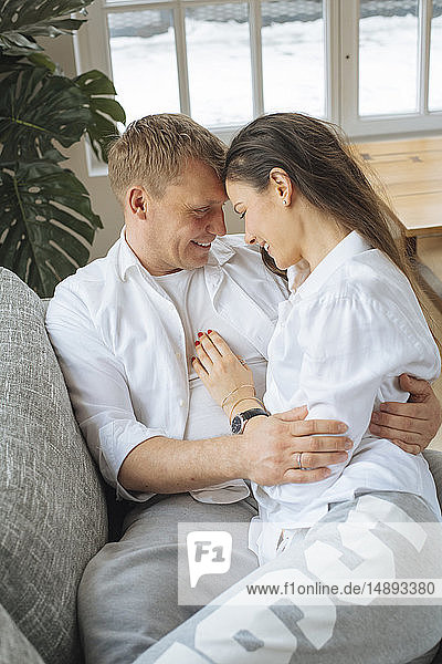 Smiling couple embracing on sofa