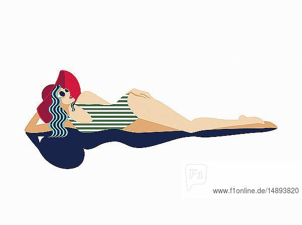 Fashion model sunbathing in striped swimsuit