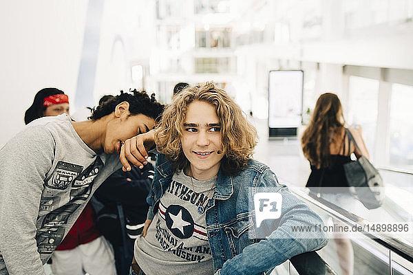 Freunde stehen auf dem Laufsteg eines Einkaufszentrums