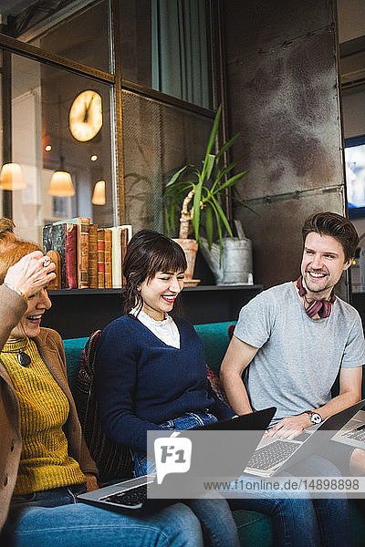 Smiling male and female colleagues looking at female manager sitting with laptop on sofa at creative office