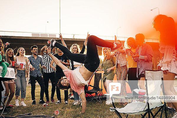 Glückliche Freunde betrachten den Mann  der im Sommer bei einer Musikveranstaltung gegen den Himmel tanzt
