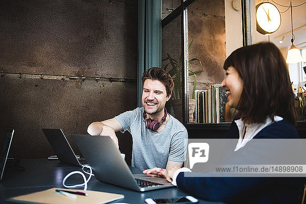 Cheerful female and male entrepreneurs discussing over laptop at desk in office