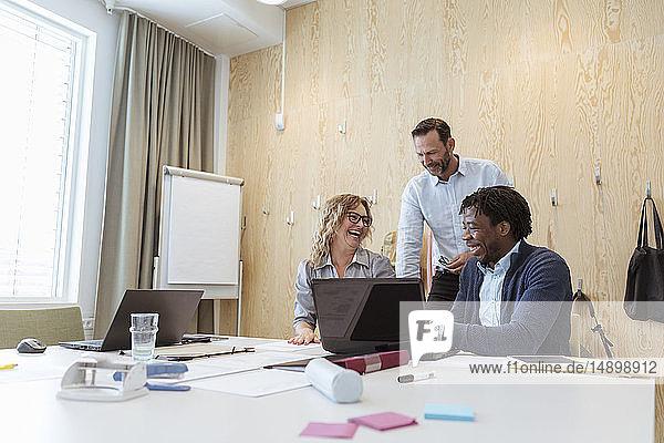 Fröhliche Geschäftskollegen sitzen am Konferenztisch im Sitzungssaal