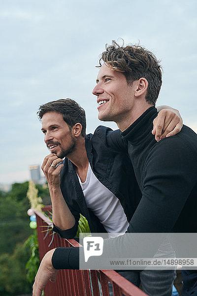 Lächelnde männliche Freunde schauen weg  während sie am Geländer auf der Terrasse gegen den Himmel stehen