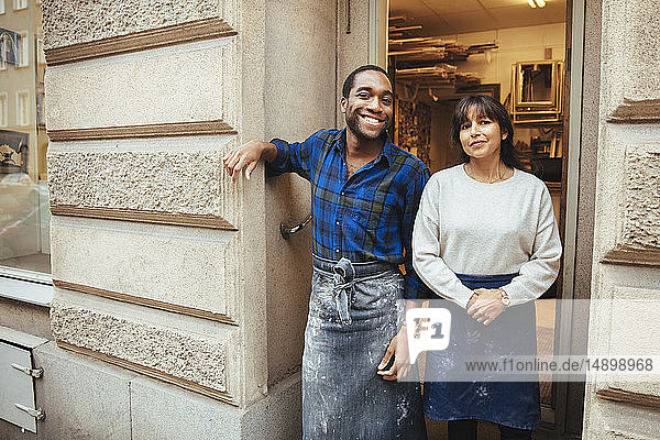 Porträt eines lächelnden Künstlers und einer lächelnden Künstlerin am Eingang zur Werkstatt