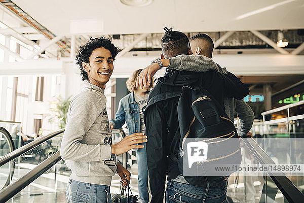 Porträt eines lächelnden Teenagers beim Einkaufen mit Freunden im Einkaufszentrum
