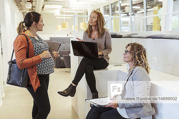 Businesswoman with laptop talking to pregnant colleague in office