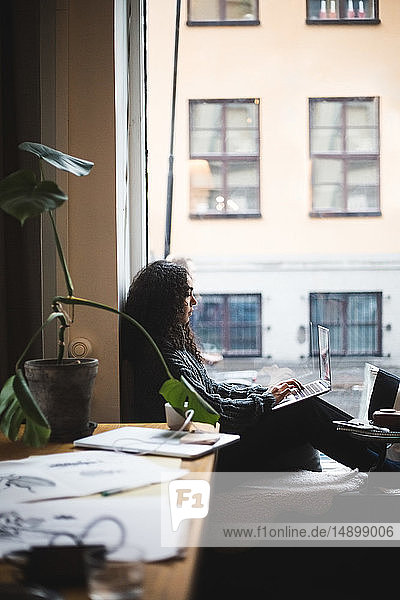 Side view of young female professional using laptop while sitting by window at office
