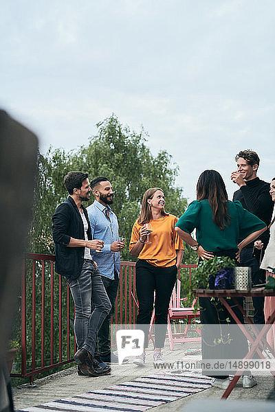Fröhliche Freunde unterhalten sich während eines geselligen Beisammenseins auf der Terrasse
