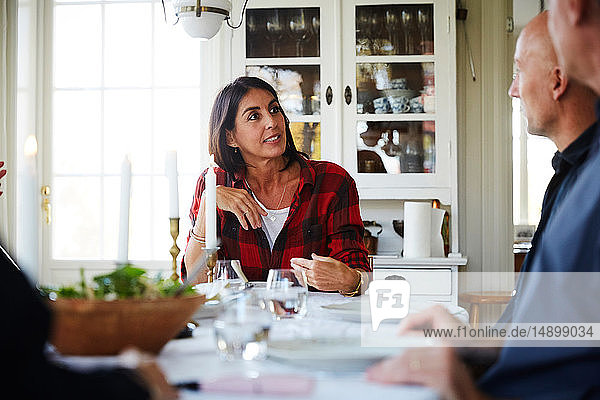 Mature woman talking with male friends while sitting at dining table