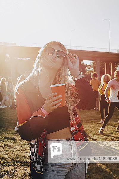 Lächelnde Frau hält Getränk in der Hand  während sie im Konzert steht