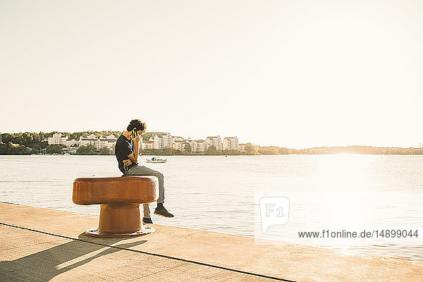 Side view of teenage boy answering mobile phone while sitting on bollard by river against clear sky during sunny day