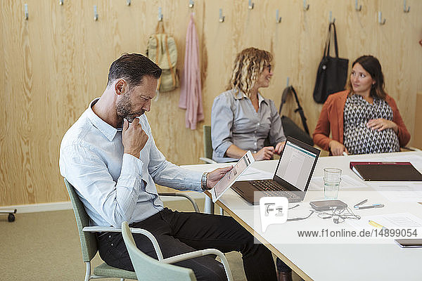 Mature professional using digital tablet while sitting with colleagues in meeting