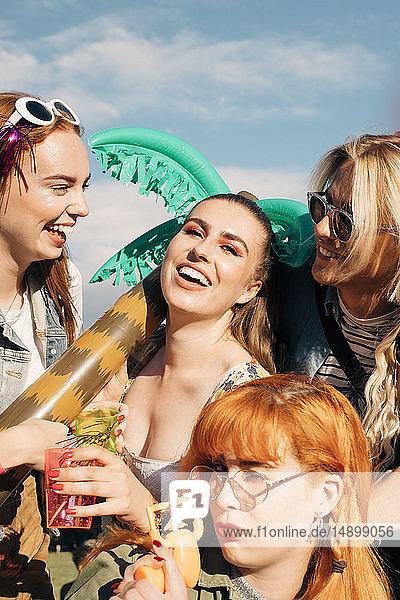Porträt von verspielten Freunden  die sich bei sonnigem Wetter am Musikfestival erfreuen