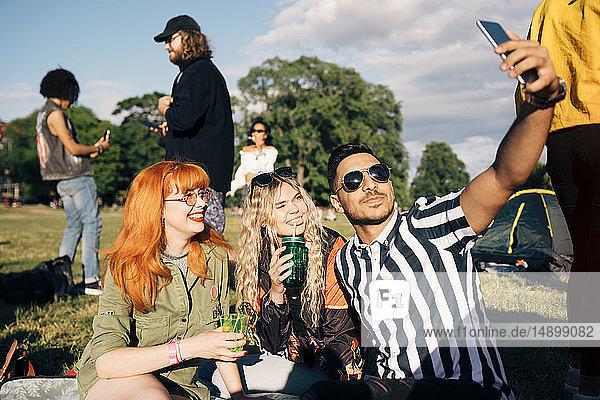 Junger Mann nimmt Selfie mit Freunden auf Smartphone während Musikkonzert im Sommer