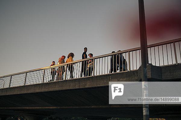 Niedrigwinkelansicht von Freunden  die auf der Brücke gegen den Himmel stehen